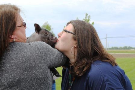 Second place money generator, Counselor Veronica Schuster, kissing Rowdy the Pig