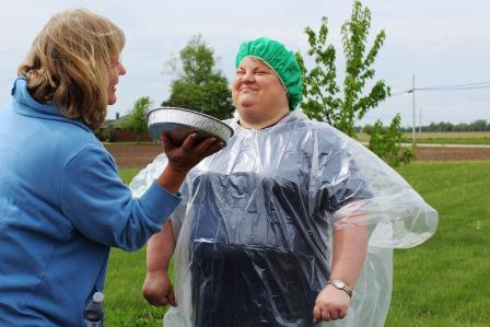 Prairie Counseling Center Director Michelle Miller preparing to get hit with her first pie by Women's Empowerment Group member Susan Haring