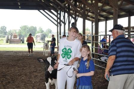4-H exhibitor Jennifer Johnson shows a calf with a young friend on Monday morning.