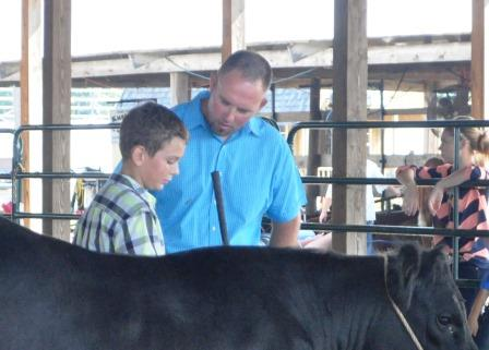 Nick Huelsmann talks with the judge during the Junior Showmanship class.  There were nine exhibitors in the 4-H junior showmanship class this year.  The largest group of exhibitors in more than ten years.