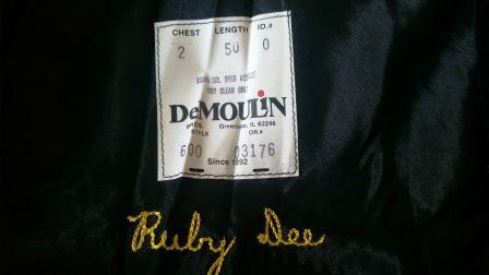 The DeMoulin manufacturing label inside the gown with Ms. Dee's name embroidered below it.